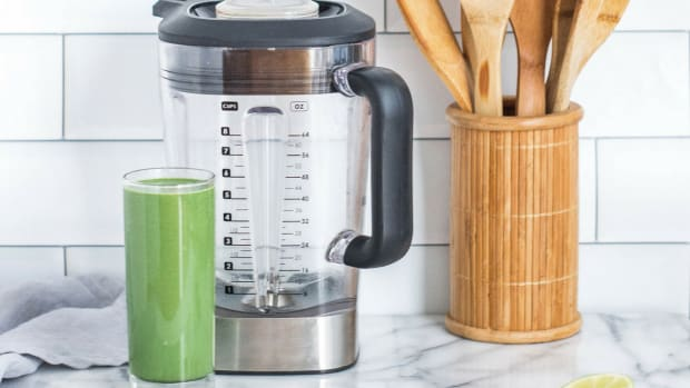 green smoothie next to blender on counter