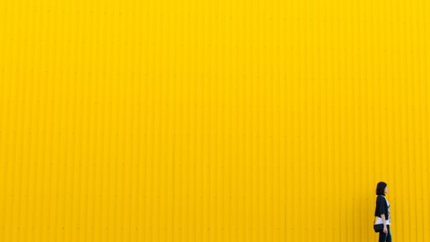 girl walking yellow wall background