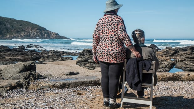 woman caregiver standing next to old person sitting on wooden chair