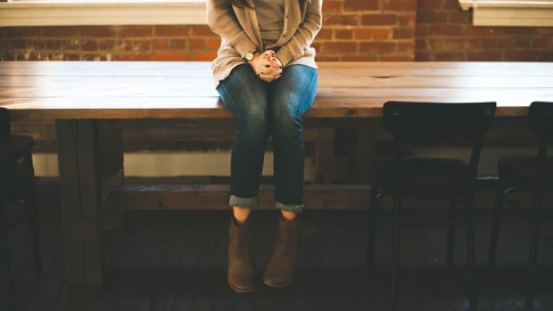 girl sitting on a table with hands crossed
