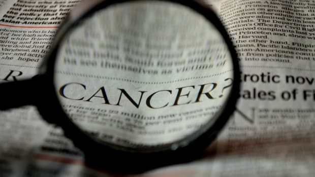 looking through magnifying glass at the word cancer