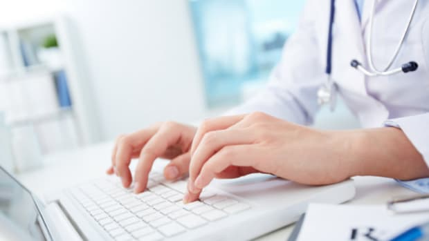 doctor typing on laptop computer at desk