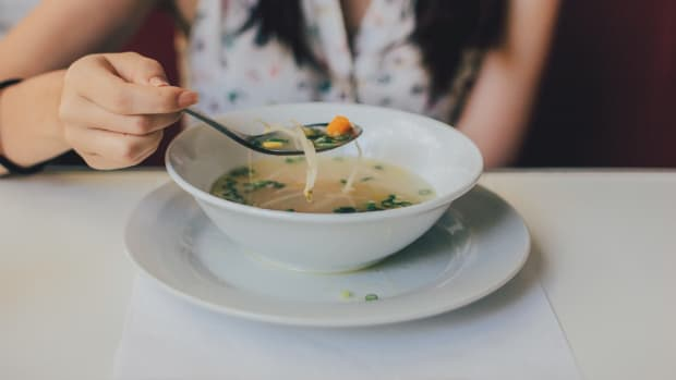 woman-in-white-tops-eating-soup-on-ceramic-bowl