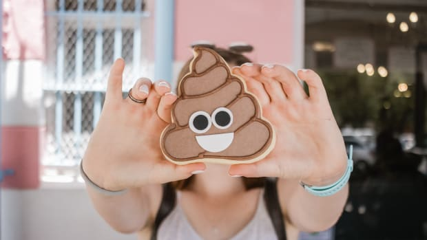 woman holding poop emoji toy