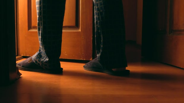 man in slippers walking into bathroom