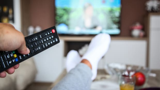 person holding remote watching tv