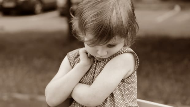 young girl in polka dot dress looking down