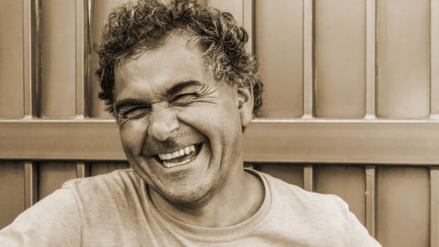Man laughing wearing a gray t-shirt