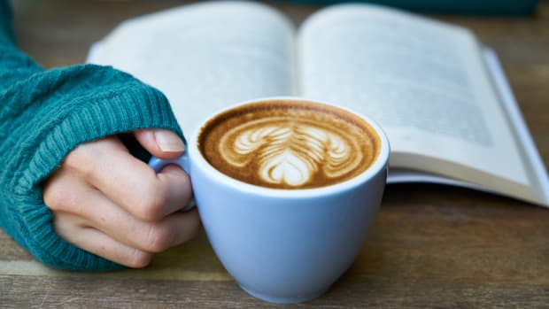 woman holding coffee cup reading a book