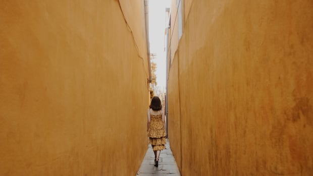 woman walking through alley with yellow walls