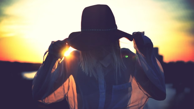 Silhouette of woman holding her hat sunset