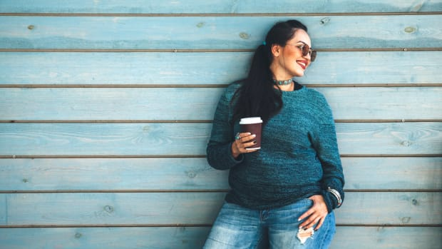 Woman smiling holding a coffee in front of blue wall