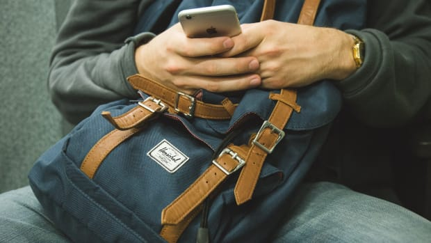 man using smartphone holding backpack