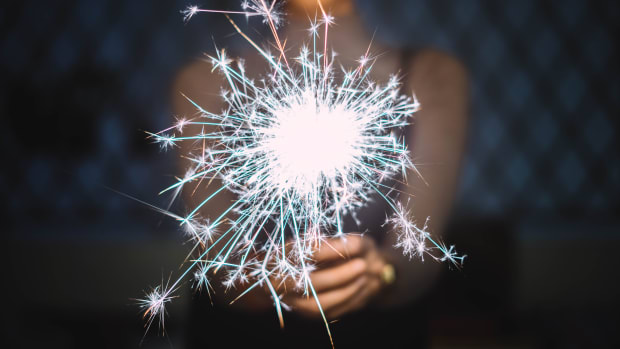 woman holding sparkler new years