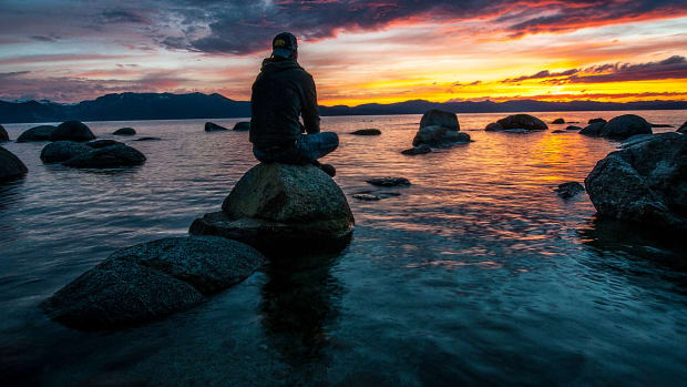man sitting on a rock in a body of water