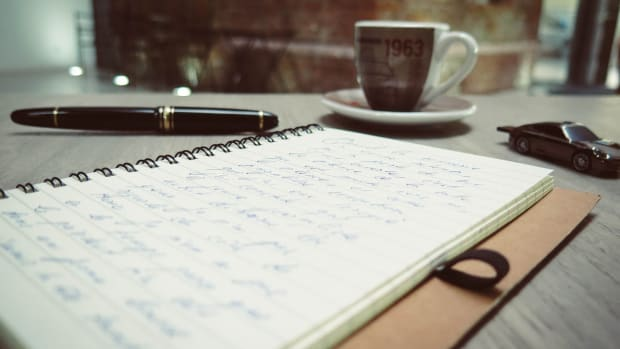 letter with pen and coffee mug on desktop