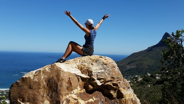 woman sitting on rock with hands up