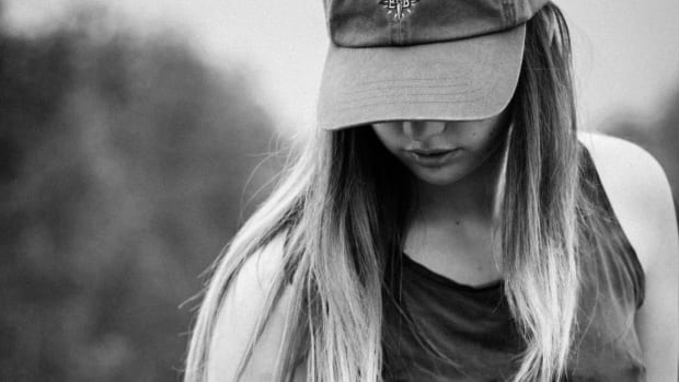 girl in cap looking at the ground