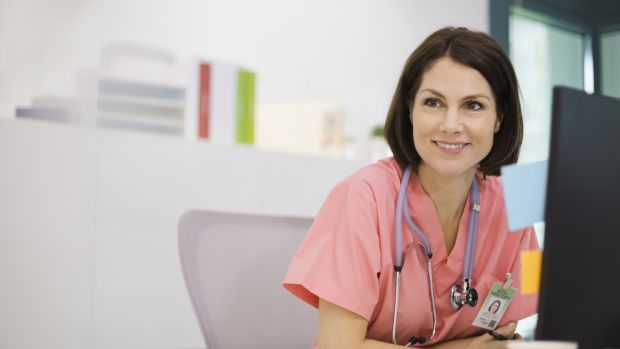 smiling nurse sitting at desk