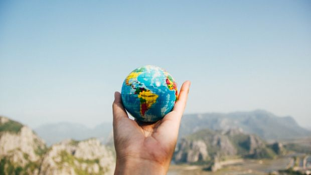 hand holding globe with blur mountain scenery