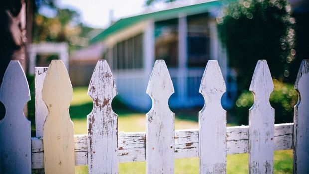white picket fence with blurred house