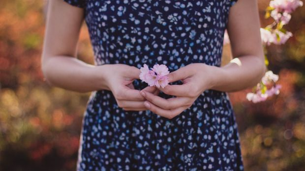 women-in-blue-and-white-floral-dress-with-pink-flower-on-hand