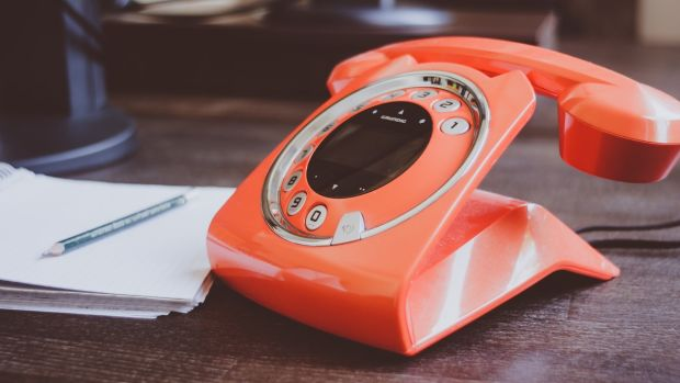 orange telephone on desk with notepad