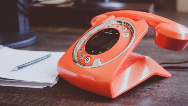 orange telephone on desk with notepad