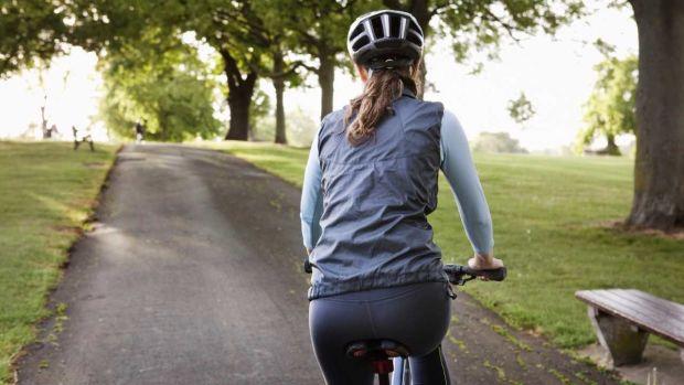 Woman riding bike on street 1280
