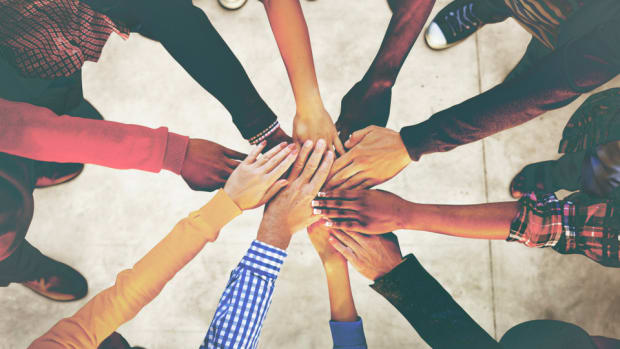 group of diverse ethnicity joining hands