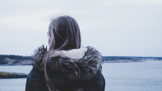 girl looking out at beach wearing coat