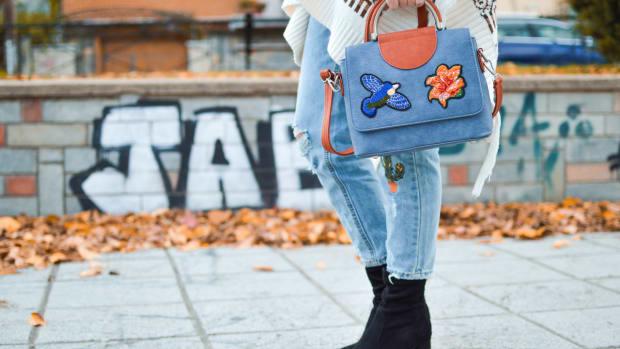 woman holding purse walking on sidewalk