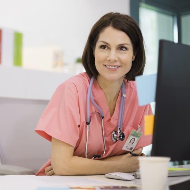 smiling nurse sitting at desk