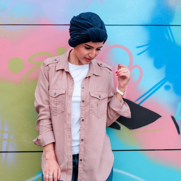 woman leaning on colorful wall
