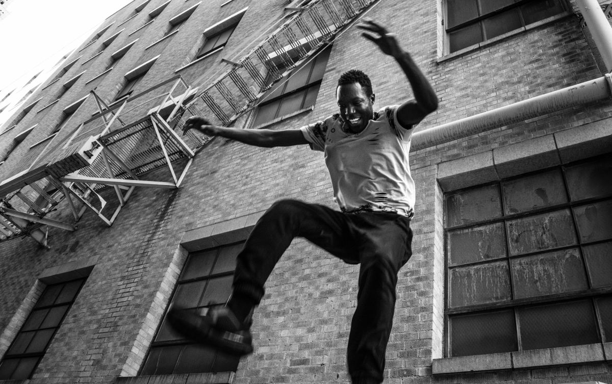 grayscale photography of African man jumping near building