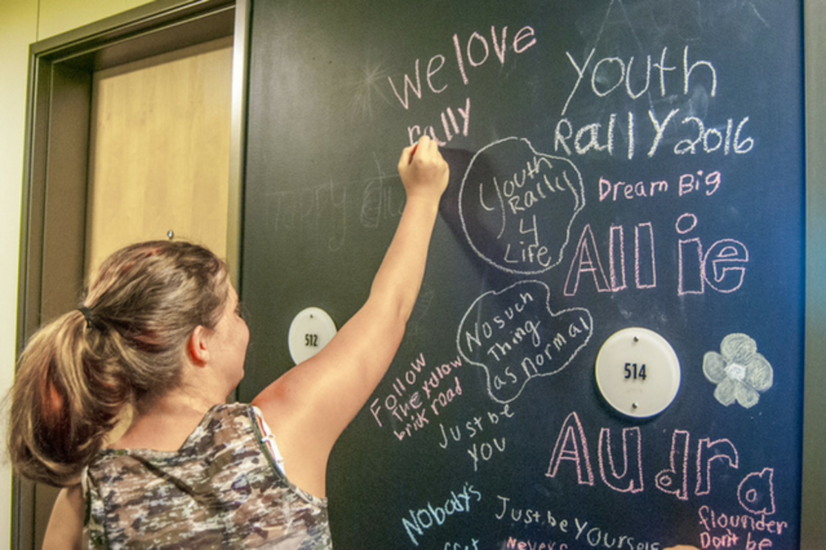 girl drawing on chalk board door sign