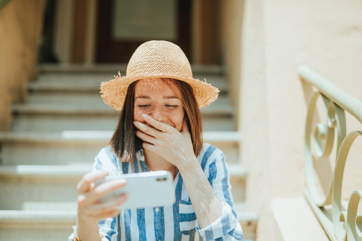 girl smiling reading Twitter on cell phone