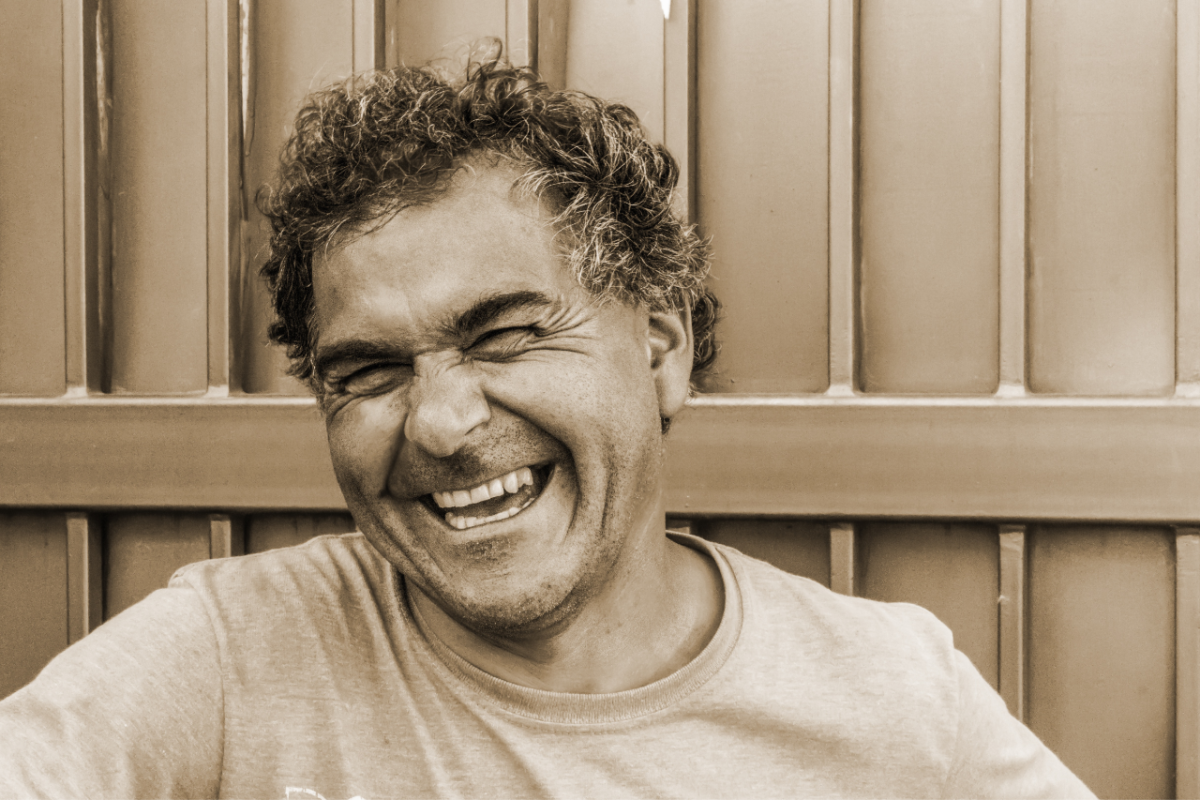 Man laughing wearing a gray t-shirt