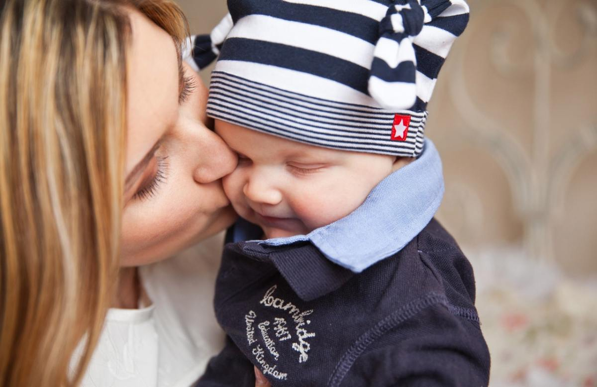 mother holding kissing infant son