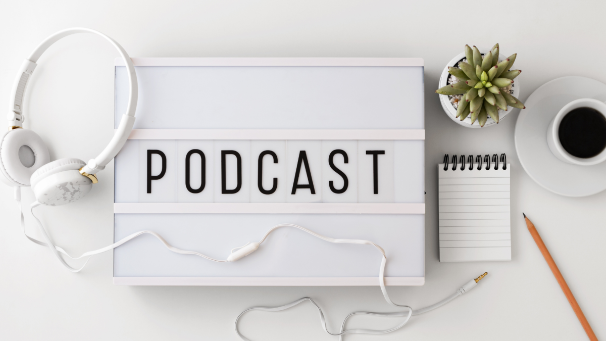 podcast with headphones and coffee on desk